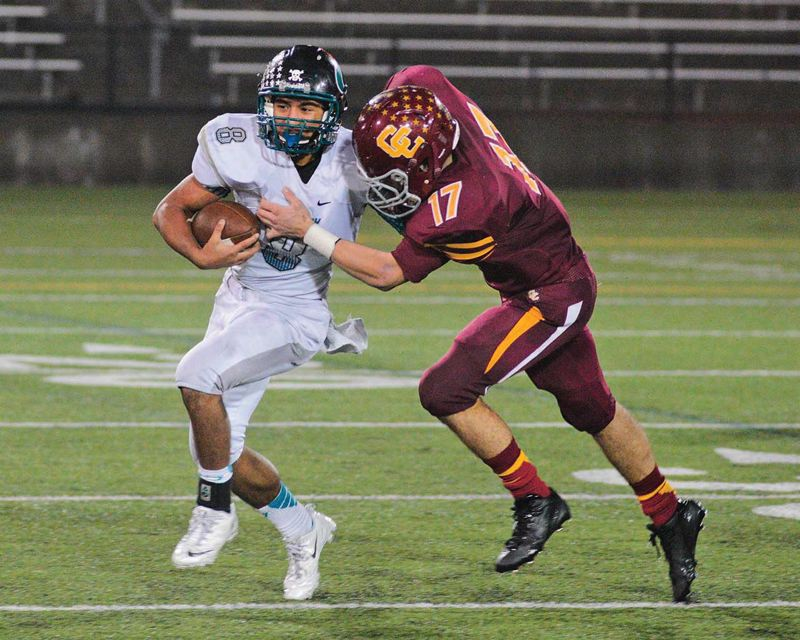 Photo Credit: PAMPLIN MEDIA GROUP: CHASE ALLGOOD - Ronnie Rust (right) brings down Century High quarterback Marcos Hernandez in a 2013 playoff game. Rust is part of a strong returning corps of linebackers for defending Class 6A champion Central Catholic.