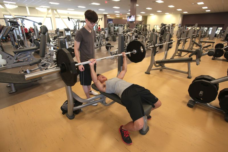 Photo Credit: TIMES PHOTO: JONATHAN HOUSE - Phi Lam lifts weights with the help of Daylem Wheeler at the new VillaSport Athletic Club and Spa on Monday.