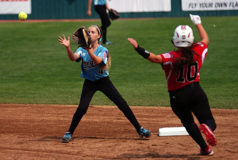 Photo Credit: DAN BROOD - CAUGHT STEALING -- Tigard/TC shortstop Bella Valdes (left) looks to grab the ball before tagging out Canada's Lauren Thomas.