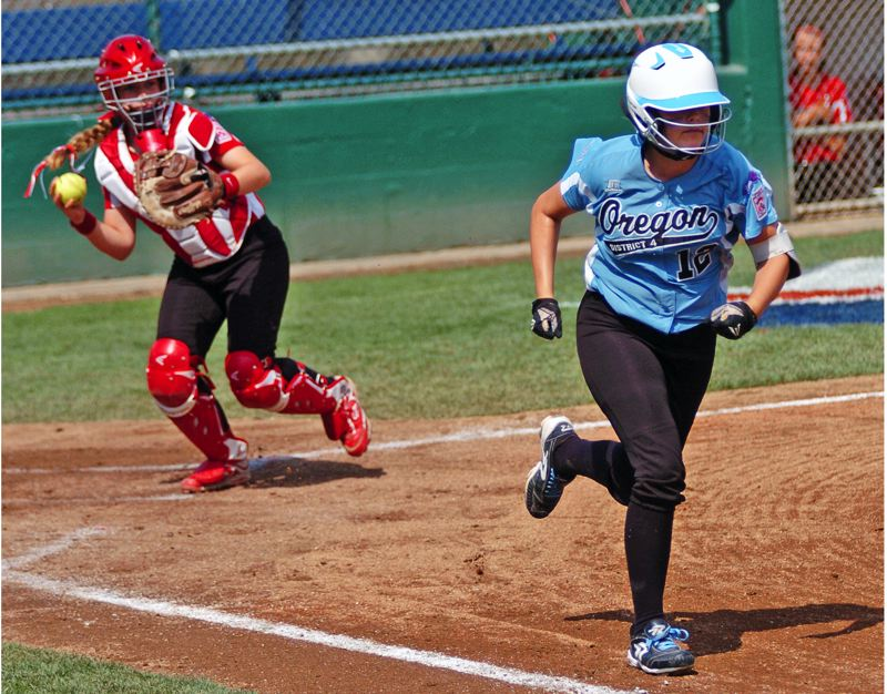 Photo Credit: DAN BROOD - SMART PLAY -- Tigard/TC's Emily Harms (right) sprints to first base after a dropped third strike in the team's game with Canada. Drawing the throw to first allowed Alexis Klum to score for the Tigard/TC squad.