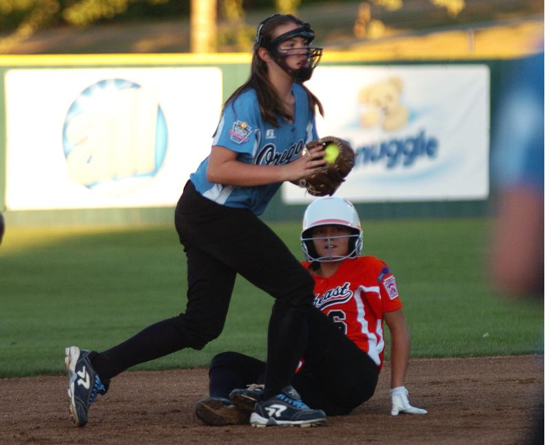 Photo Credit: DAN BROOD - Tigard/TC second baseman Logan Mentzer (left) put out Georgia's  Jillian Holloway during World Series action.