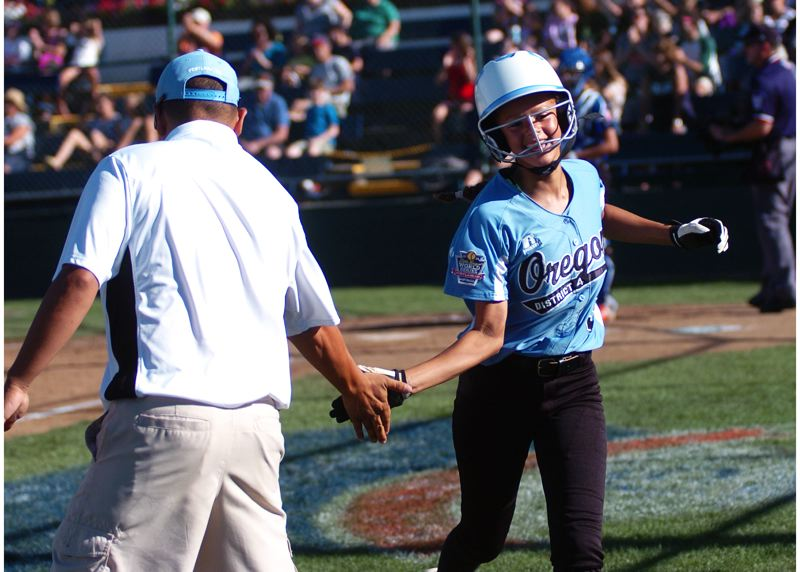 Photo Credit: DAN BROOD - Tia Cordts is congratulated by her father, Tigard/TC manager Chris Cordts, after she scored a run during the team's win over Prague.