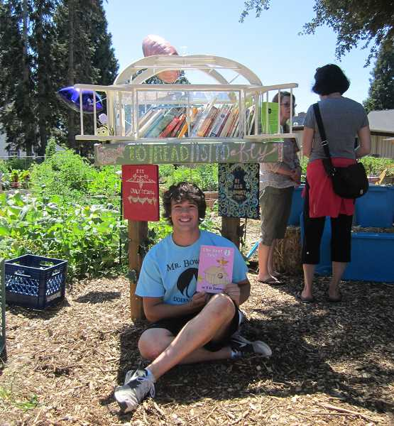 Photo Credit: GAZETTE PHOTO: BARBARA SHERMAN - Kes Rooney, who designed and built an outdoor bookstand outside the Bethlehem House of Bread that will become part of the Little Free Library system, reads a childhood favorite, 'The Best Nest,' during the July 31 dedication ceremony.