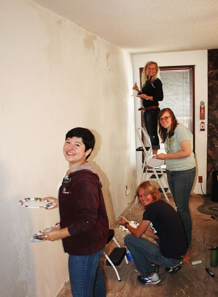 Photo Credit: CONTRIBUTED PHOTO: RICH ALLEN - Young women from a Latter-day Saints church group sand and prime an aging wall in the Lowes living room.