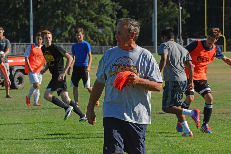 Photo Credit: JOHN WILLIAM HOWARD - Bob Opperman, the new boys soccer coach at St. Helens High School, looks on as the team scrimmages during practice this week.