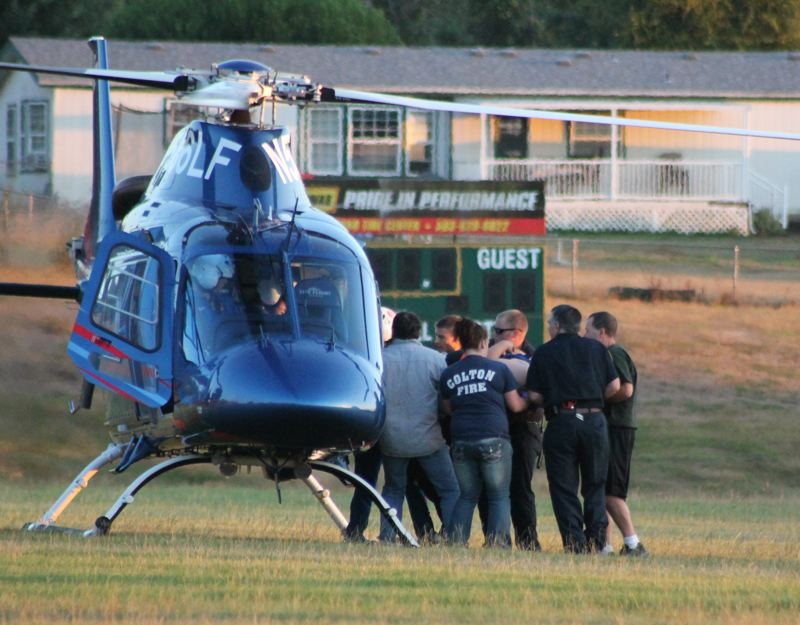Photo Credit: JIM BESEDA/MOLALLA PIONEER - Emergency personnel from Colton Rural Fire Protection District No. 70 and Molalla Rural Fire Protection District No. 73 assisted in getting a Colton High School football player aboard a Life Flight helicopter after he sustained a neck injury at Friday's practice.