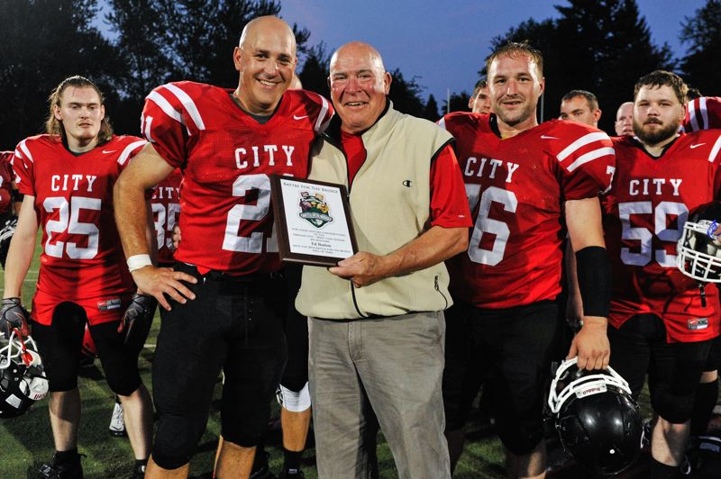 Photo Credit: JOHN LARIVIERE - Former Oregon City coach Ed Burton poses proudly with Oregon City alumni after being inducted into the Battle for the Bridge Hall of Fame at halftime of the 2014 Battle for the Bridge alumni game. Pictured with Burton are (from left) Doug Millard (25), Michael Canchola (21), Lucas Spooner (76) and Nick Shafer (59).