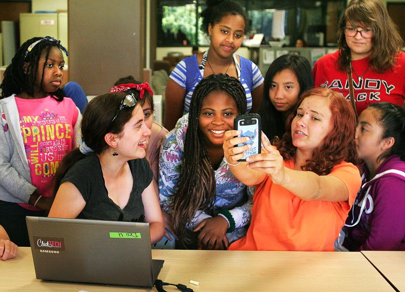Photo Credit: OUTLOOK PHOTO: JIM CLARK - Hailey Freeman, with sunglasses on her forehead, and Madelynn Young, right, explain the phone app they created during their four-week STEM learning camp. Garmony Endambo is in the center.