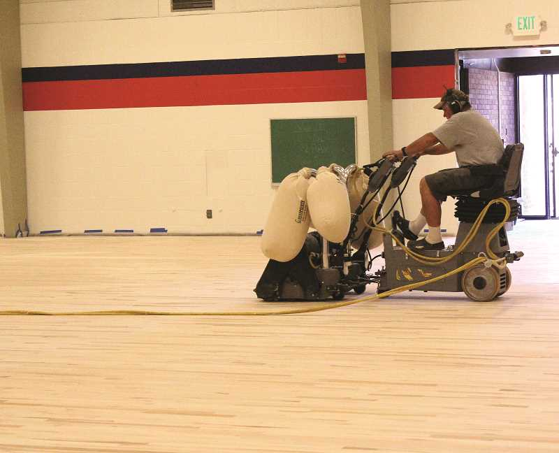 Photo Credit: LINDSAY KEEFER - A construction worker smooths the newly laid gym floor at Mount Angel Middle School. The gym will now meet regulations, and students will no longer have to play sports on a concrete floor.