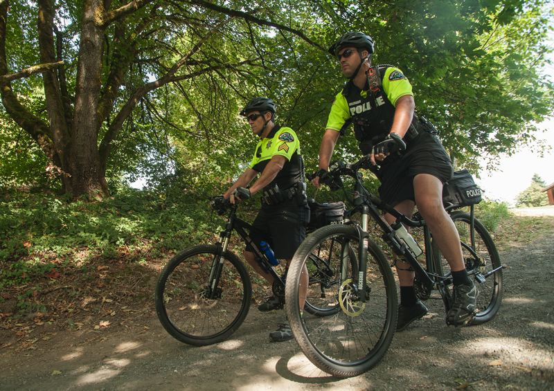 Photo Credit: SPOKESMAN PHOTO: JOSH KULLA - Wilsonville Police Sgt. Dan Kraus, left, and Officer John Wildhaber, right, say that residents find them more approachable when they patrol on bikes.