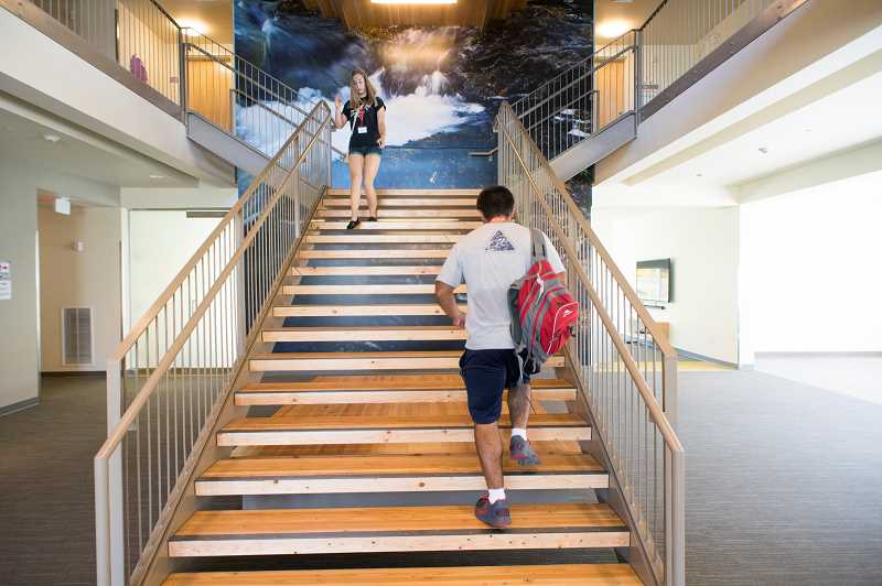 Photo Credit: NEWS-TIMES PHOTOS: CHASE ALLGOOD - Residents of the new Cascade Hall at Pacific University come and go on the main stairwell, in front of the bottom section of a four-story photo mural that inspired the residence halls name. Jim Flory, a photography professor at Pacific, shot the photo of one of the north-side waterfalls in Silver Falls State Park near Silverton, Oregon. The recently completed hall represents a move away from the newer pod-style arrangements at many universities and back to old-style, shared rooms that will encourage students to engage more in community experiences at the halls many recreational and study areas, as well as at the nearby University Center. An estimated 565 new undergraduates began classes at Pacifics Forest Grove campus Monday, bringing total enrollment there to more than 1,700.