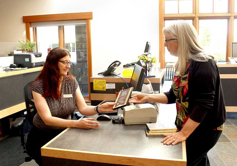 Photo Credit: POST PHOTO: LAURA KNUDSON  - Libby Burke, research librarian at Bonneville Power Administration, presents free copies of the hydroelectric DVD series to Monica Smith, Sandy librarian.