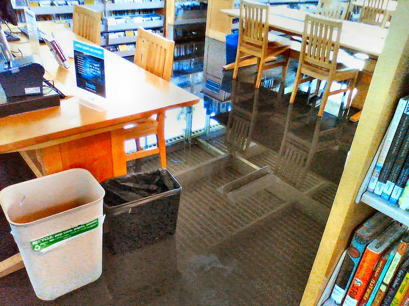Photo Credit: COURTESY OF PETER FORD - Chairs and ceiling are reflected in standing water at the Woodstock Branch Library after it flooded in the night.