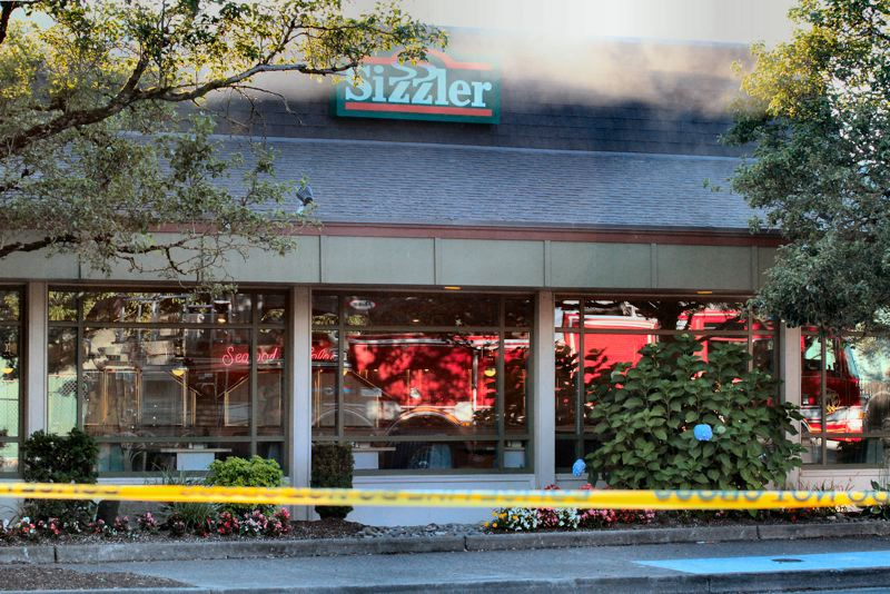 Photo Credit: DAVID F. ASHTON - The smoke pouring over this Sizzler restaurant wasnt from burned steak; the back of the building was on fire.