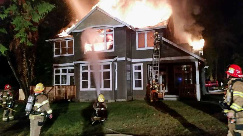 Photo Credit: SUBMITTED PHOTO: TUALATIN VALLEY FIRE & RESCUE - Fire engulfed an unoccupied two-story home early Wednesday morning, causing the roof to collapse.