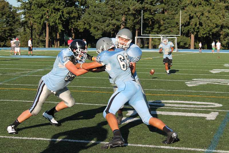 Photo Credit: REVIEW  PHOTO: JILLIAN DALEY - Lakeridge player Beau Bryant, left, grapples with and Jack Holum while Camden Wulf reaches out to both players during practice Tuesday. The long shadow cast at the young men's feet is that of defensive line coach coach Tim Price.