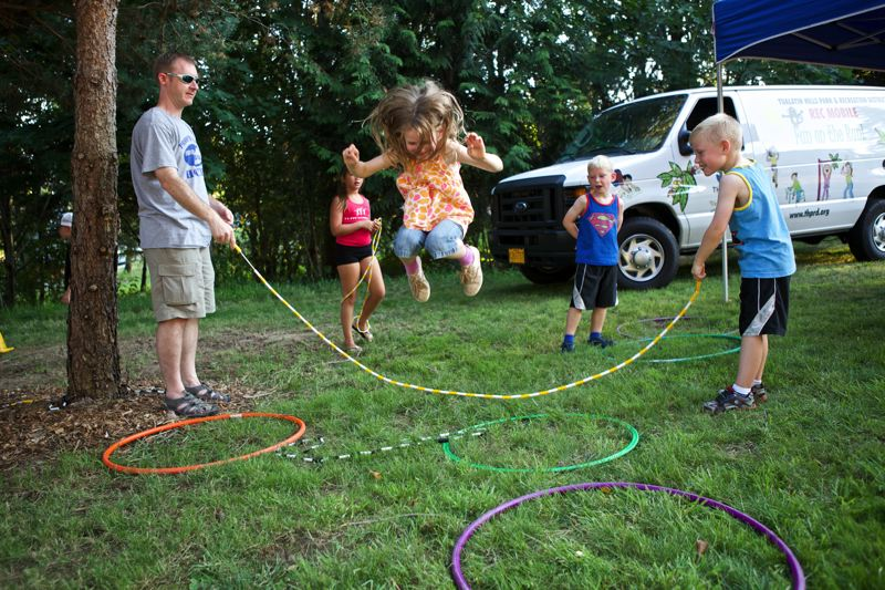 Photo Credit: TIMES PHOTO: JAIME VALDEZ - Cora Hood, 7, jumps rope for the first time with help from her dad, Luke, and her brother, Alton, 5, during the grand opening of Hansen Ridge Park.