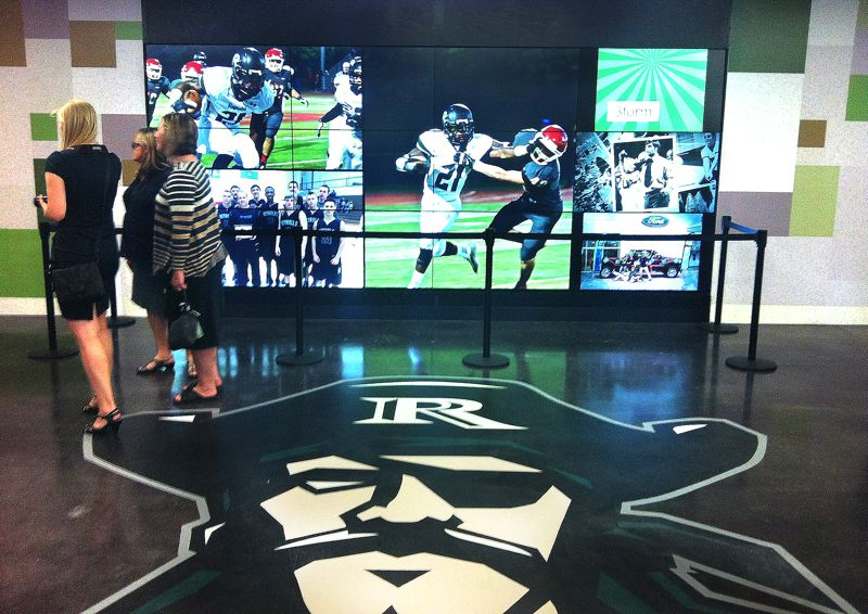 Photo Credit: OUTLOOK PHOTO: LISA K. ANDERSON - In the heart of the renovated gym lobby at Reynolds High School is the Raider mascot in front of a 12-screen media wall. Trophy cases with school memorabilia line the entryway.