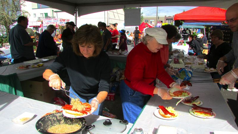 Photo Credit: FILE - From left, volunteers Carol Schuler, Neta Barbour, Martha Stokes and Brian Rosenthal dish up plates of the famous Scappoose Sauerkraut Sandwich at last year's Scappoose Sauerkraut Festival.