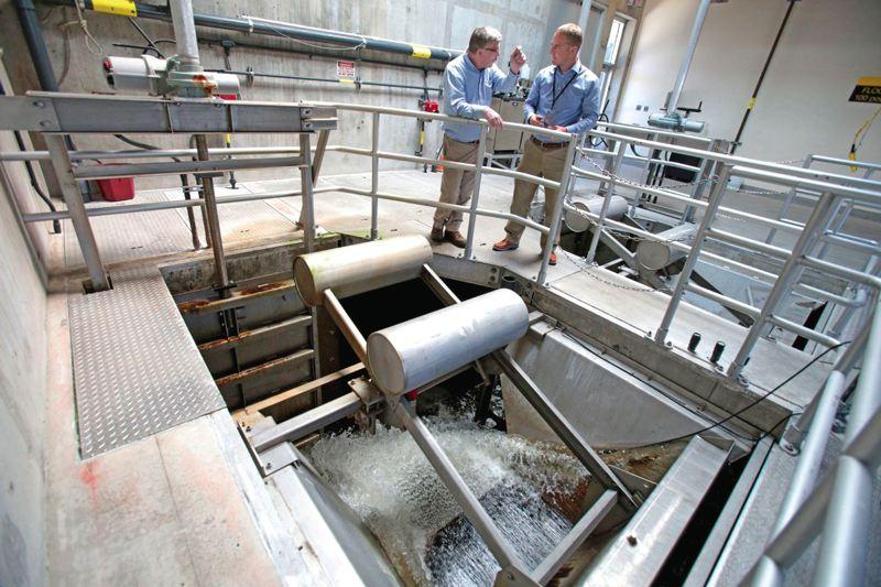 Photo Credit: PHOTO BY JONATHAN HOUSE - Clackamas Countys Ryan Johnson and Michael Trent talk as filtered water rumbles underneath at the Tri-City Water Pollution Control Plant in Oregon City. The county is taking legal action to stop an Oregon City fee for the service districts sewer lines.
