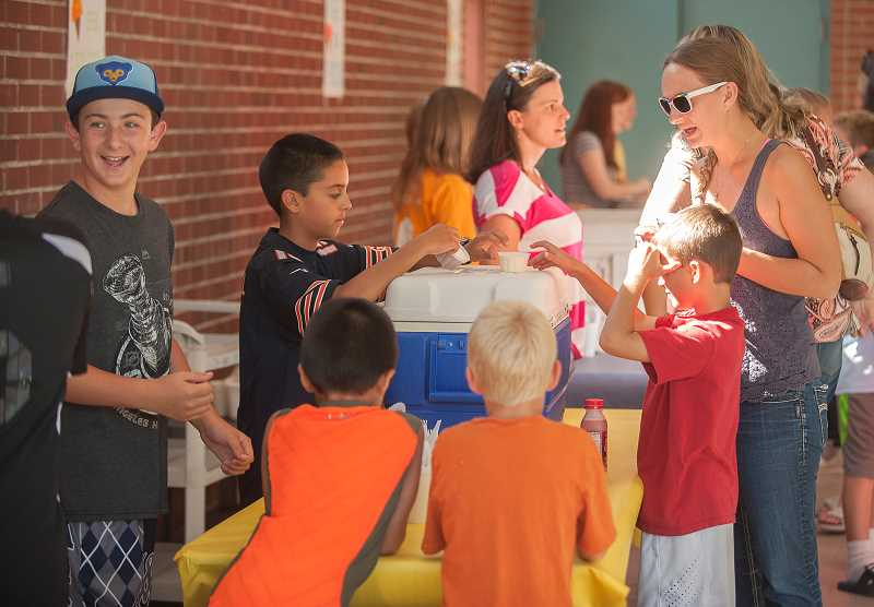 Photo Credit: SPOKESMAN PHOTO: JOSH KULLA - Students Bryan Rector, right, and Austin Giron serve ice cream to eager kids Aug. 28 at Boeckman Creek Primary Schools ice cream social.