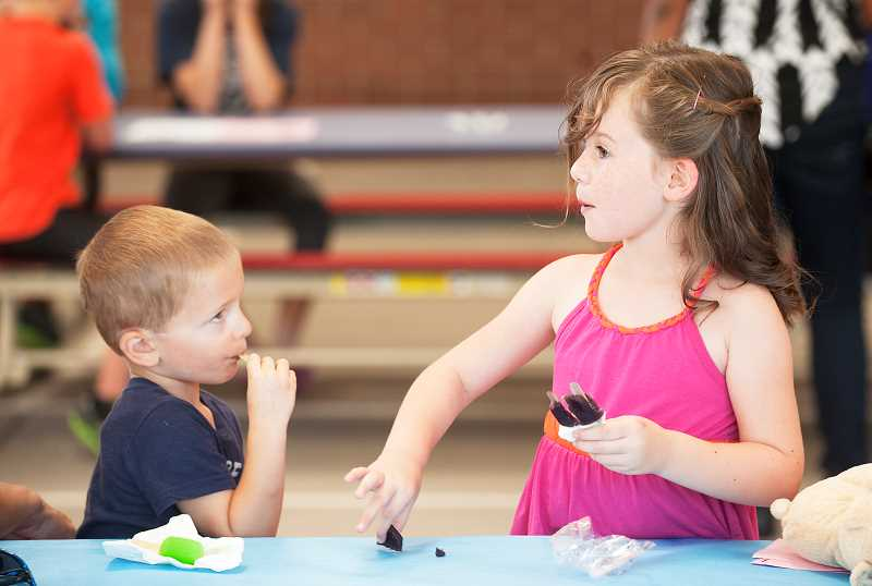 Photo Credit: SPOKESMAN PHOTO: JOSH KULLA - Molly Foster (R) and Jake Carroll wonder whether they can get more ice cream last Thursday at Boeckman Creek Primary Schools back-to-school ice cream social.