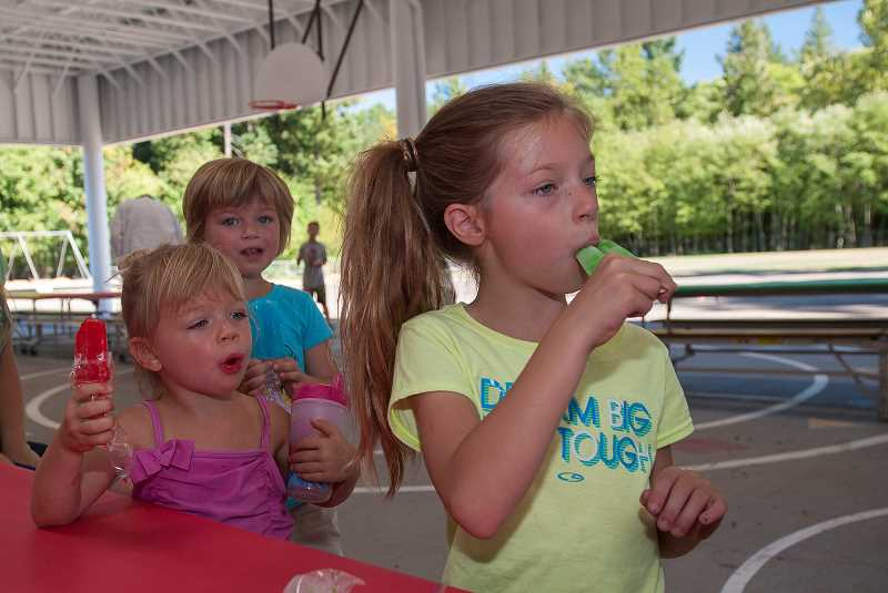 Photo Credit: SPOKESMAN PHOTO: JOSH KULLA - Ceili Friedman, a Boeckman Creek third-grader, gobbles down a popsicle Thursday at her schools ice cream social. Behind her are sisters Martha (middle), a kindergartner, and Josephine, 2.