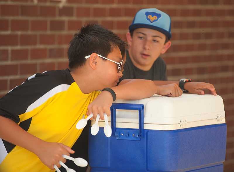 Photo Credit: SPOKESMAN PHOTO: JOSH KULLA - Kyle Lam and Bryan Rector, left, wait to serve ice cream Thursday at Boeckman Creek Primary School.