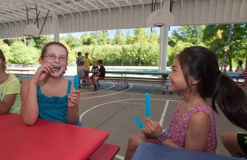 Photo Credit: SPOKESMAN PHOTO: JOSH KULLA - Chloe Lam (right) and Grace Friedman enjoy a last bit of summer fun together at Boeckman's back-to-school ice cream social Aug. 28.