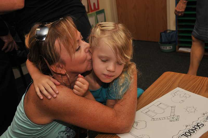 Photo Credit: REVIEW PHOTO: VERN UYETAKE - Michelle Huntington gives her daughter, Michelle, a big kiss before leaving her on her first day of second grade at Hallinan Elementary.