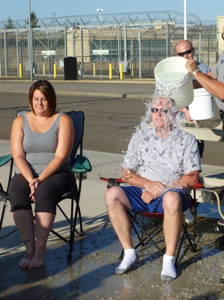 Photo Credit: SUBMITTED PHOTO - Coffee Creek Correctional Facility Assistant Superintendent of Security Dennis Caswell undergoes the Ice Bucket Challenge Aug. 8 outside the prisons minimum security wing while Amanda Mooney watches nervously.