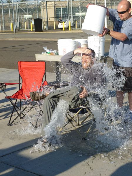 Photo Credit: SUBMITTED PHOTO - Coffee Creek Correctional Facility employee Dave Brown takes the Ice Bucket Challenge at the hands of fellow employees Aug. 8 outside the prisons minimum security wing.