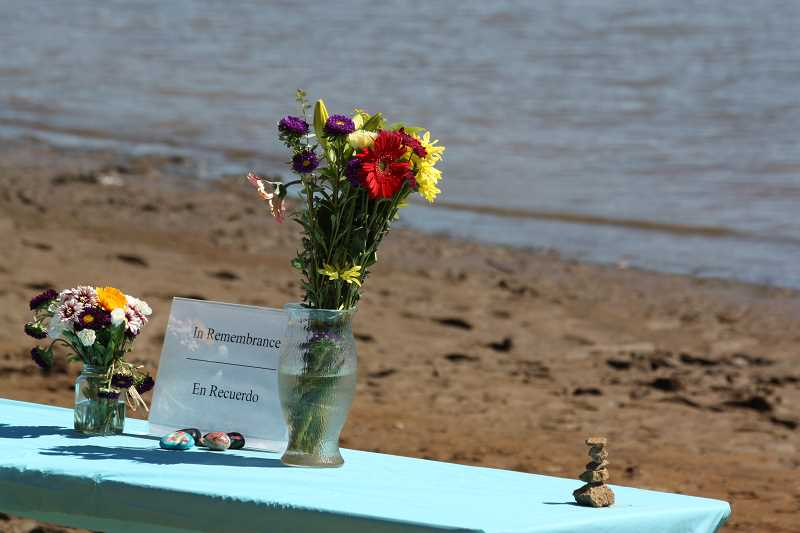 Photo Credit: NEWS-TIMES PHOTO: DOUG BURKHARDT - Forest Grove mother Robbie Pock added flowers Thursday to a memorial at the Sain Creek Picnic Area last week. The flowers joined some Love Rocks, a local craft and outreach phenomenon that sprang from the deaths of two Forest Grove sisters last year. Pocks daughter played in the water (pictured) while wearing a life jacket. Be aware it might drop off quickly, so go slowly, her mom called.