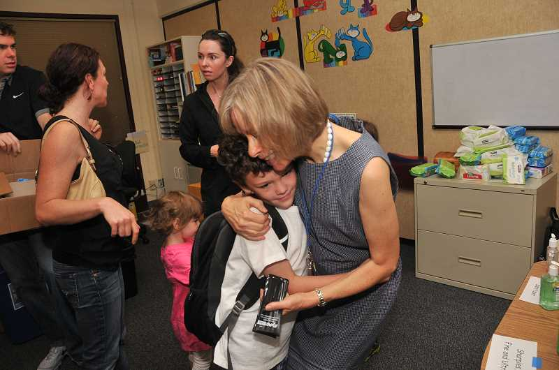 Photo Credit: REVIEW PHOTO: VERN UYETAKE - Charlie Wakefield gets a warm welcome from his second-grade teacher, Diane Mather.