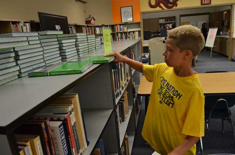 Photo Credit: REVIEW PHOTO: VERN UYETAKE - Sixth-grader Carson Campbell checks out his textbook on the first day of school at LOJHS.