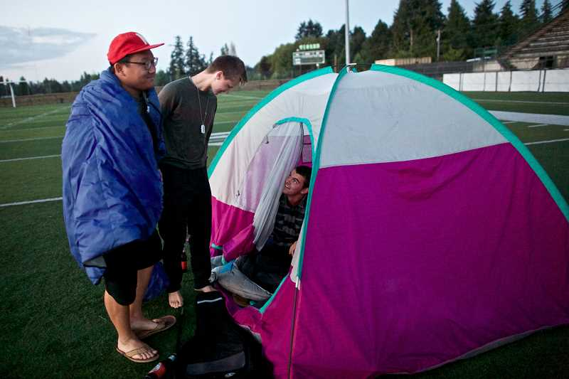 Photo Credit: TIMES PHOTO: JAIME VALDEZ - Jimmy Ha, Cole Cameron and Nick Stevens wake up after sleeping in a tent overnight on the football field at Tigard High School. School officials say its the first year anyone has camped out the evening before Senior Sunrise.