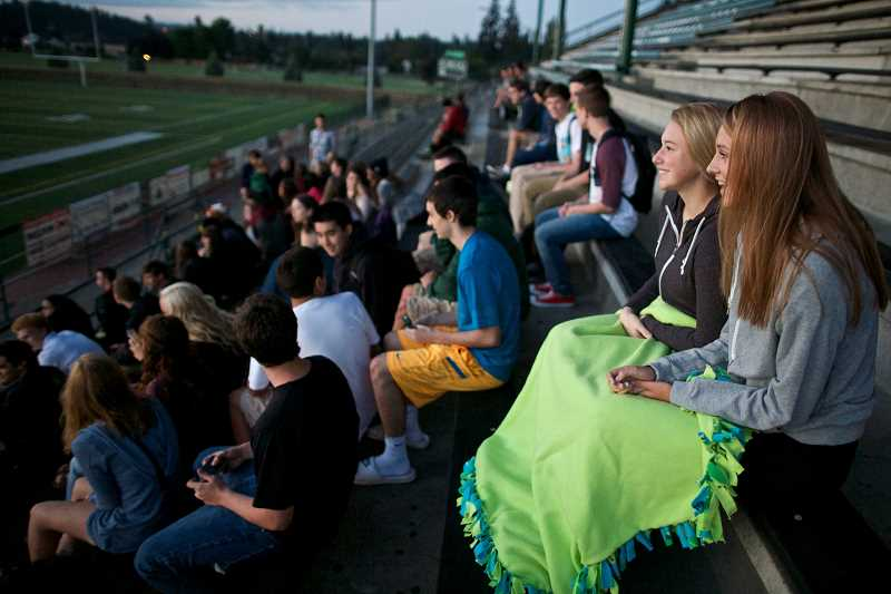 Photo Credit: TIMES PHOTO: JAIME VALDEZ - Emilee Heyden and Sarah Schaffer sit with their senior class to watch the sunrise on the first day of school at Tigard High School. The tradition goes back at least 15 years, but school officials say they arent sure when it began.