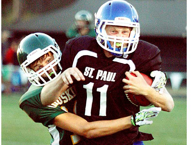 Photo Credit: PHIL HAWKINS - Shaking free - St. Paul quarterback Cody Faber attempts to shred a tackler at the Bucks' preseason jamboree on Friday. The Bucks will make their 2A debut Friday at home versus Crow.