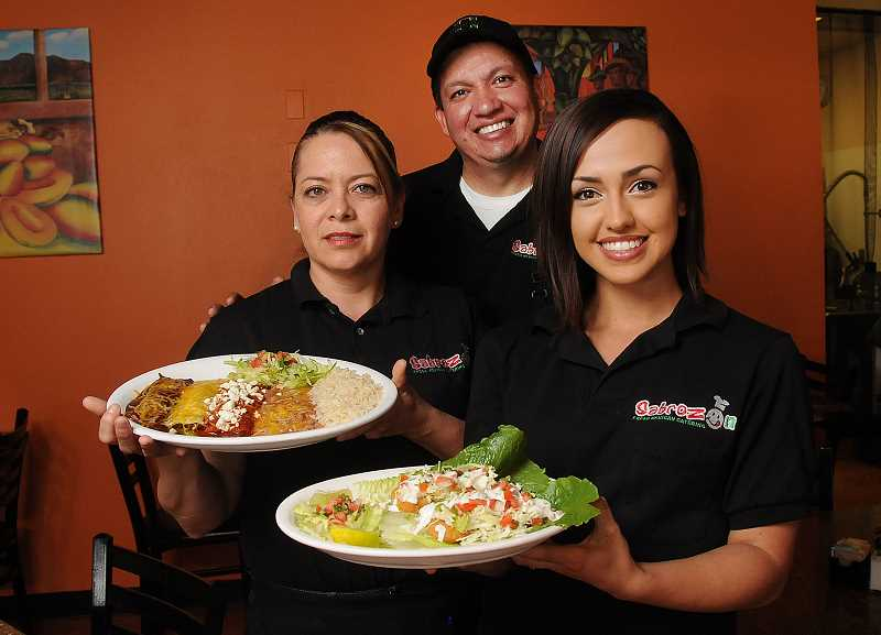 Photo Credit: STAFF PHOTOS: VERN UYETAKE - Sabrozon owners Maggie and Raul De La Torre and their daughter, Amber Rago, show off some of the items on their menu.