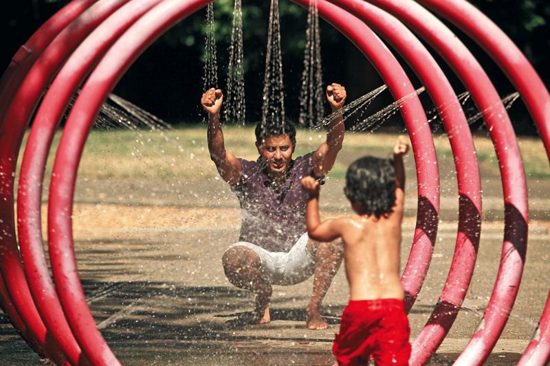 Photo Credit: TRIBUNE PHOTO: JAIME VALDEZ - Vivek Shandas, associate professor at PSUs Toulan School of Urban Studies and Planning, hangs out with his son, Suhail, at the water fountain at Essex Park in Southeast Portland. Shandas is leading an effort to study and combat Portlands urban heat island problem.
