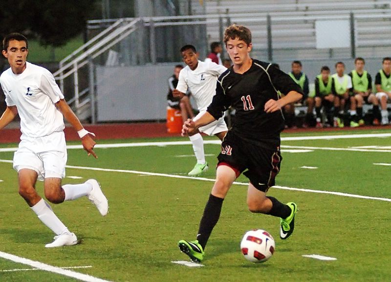 Photo Credit: DAN BROOD - BACK FOR THE WOLVES -- Junior midfielder Alex Bruce, shown here in a match from the 2013 season, is one of a few returning varsity players for the Tualatin High School boys soccer team.