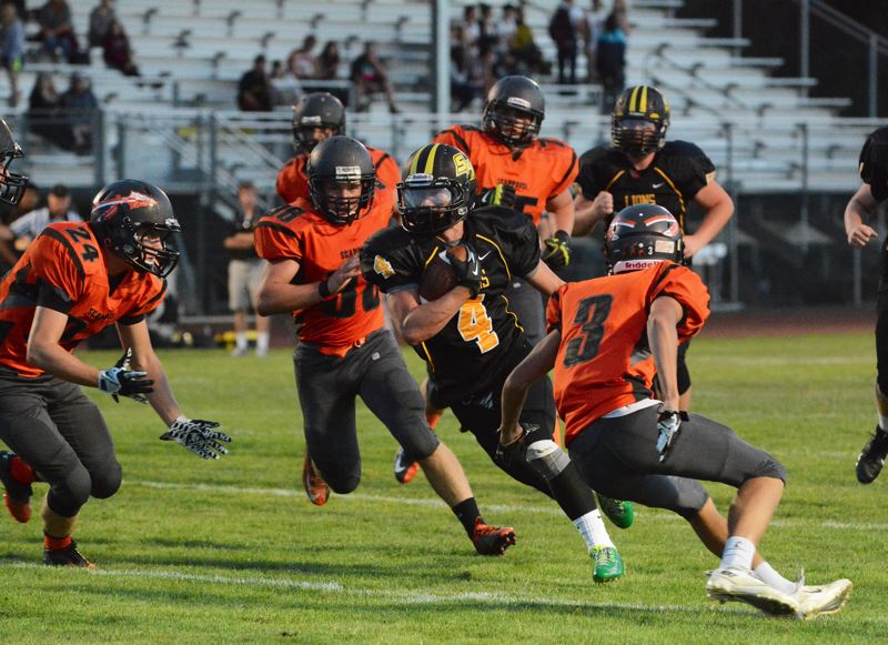 Photo Credit: JOHN WILLIAM HOWARD - St. Helens sophomore running back Myles Terry looks to escape the Scappoose defense during a jamboree on Aug. 29.