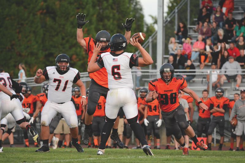 Photo Credit: JOHN WILLIAM HOWARD - Scappoose junior defensive tackle Keenan Stevens takes a leap in front of RA Long quarterback Ryan Peerboom, looking to force him into a quick pass, or bat down a potential deep threat. The Indians will focus on getting in the face of 6-foot-4 Cascade quarterback John Schirmer with the hope that it will disrupt the Cougars' offensive rhythm and lead to a mistake prone game for the visitors on Friday night.