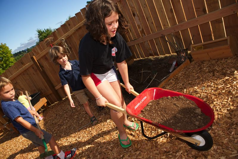 Photo Credit: TIMES PHOTO: JAIME VALDEZ - Payden Randall and Jackson De Salvo, both 4, watch 9-year-old Bennett Crawford push a wheelbarrow at the preschool playground at St. Gabriel the Archangel Episcopal Church.
