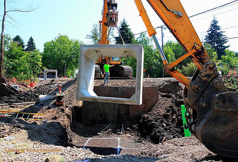 Photo Credit: DOUG VORWALLER -  Crews install a large culvert under Southwest Walnut Street as part of a restoration of Derry Dell Creek. The project is expected to last through this week, with several other construction projects happening across the city