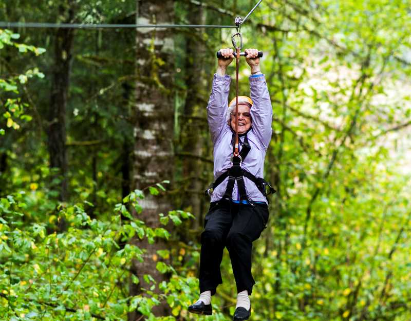 Photo Credit: NEWS-TIMES PHOTO: CHASE ALLGOOD - Toni Gerbracht, 88, rides a zip line at Tree to Tree Adventure Park near Hagg Lake as part of an excursion during Active Aging Week Sept. 24.