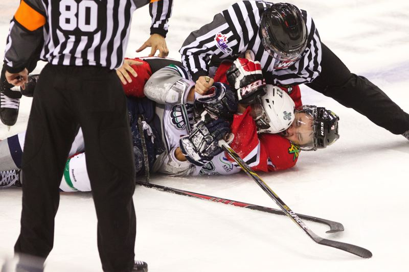 Photo Credit: TRIBUNE PHOTO: JAIME VALDEZ - Defenseman Josh Hanson (right) of the Portland Winterhawks grapples with Seattle's Evan Wardley after Wardley took down the Hawks' Nicolas Petan during the first period Saturday night at Moda Center.