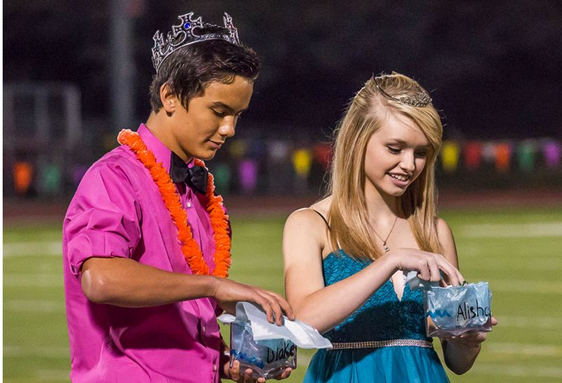Photo Credit: HILLSBORO TRIBUNE PHOTO: RICK PAULSON - At Glencoe High, homecoming court members included freshmen Blake Lee and Alisha Bender, who peeked into goodie bags provided for them by the school during the big game against Sunset last weekend. The Apollos werent denied a win as they beat the Crimson Tide 63-21.