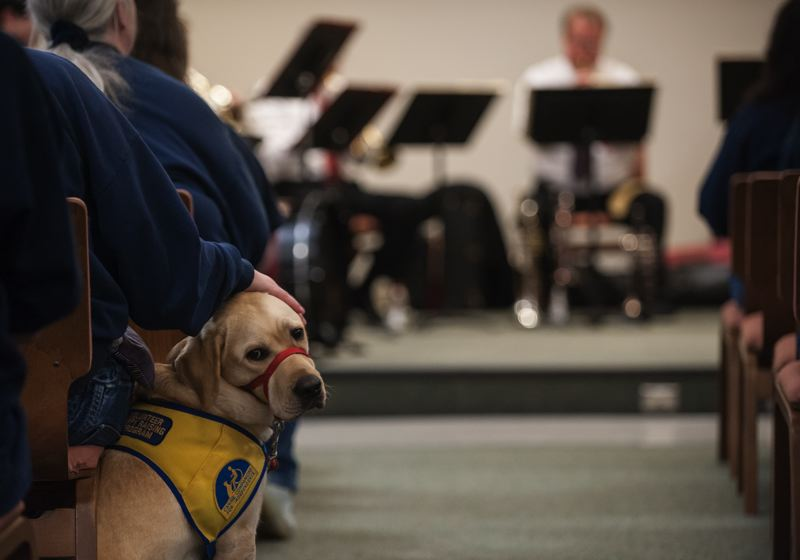 Photo Credit: SPOKESMAN PHOTO: JOSH KULLA - Coffee Creek is home to a puppy training program – the dogs go everywhere with the inmates they are assigned to live and train with – even the Dec. 9 Christmas concert performed by an Oregon Symphony quintet.