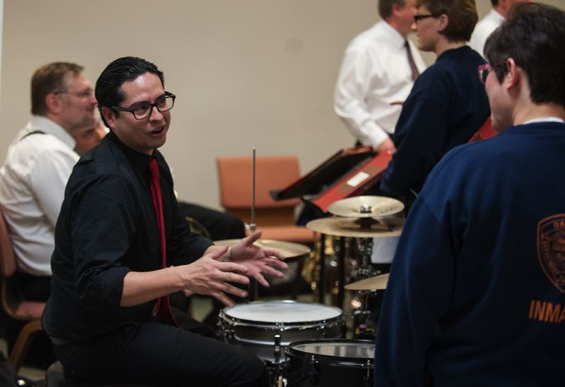 Photo Credit: SPOKESMAN PHOTO: JOSH KULLA - Oregon Symphony percussionist Sergio Carrena (left) chats with a Coffee Creek Correctional Facility inmate at a special holiday concert.